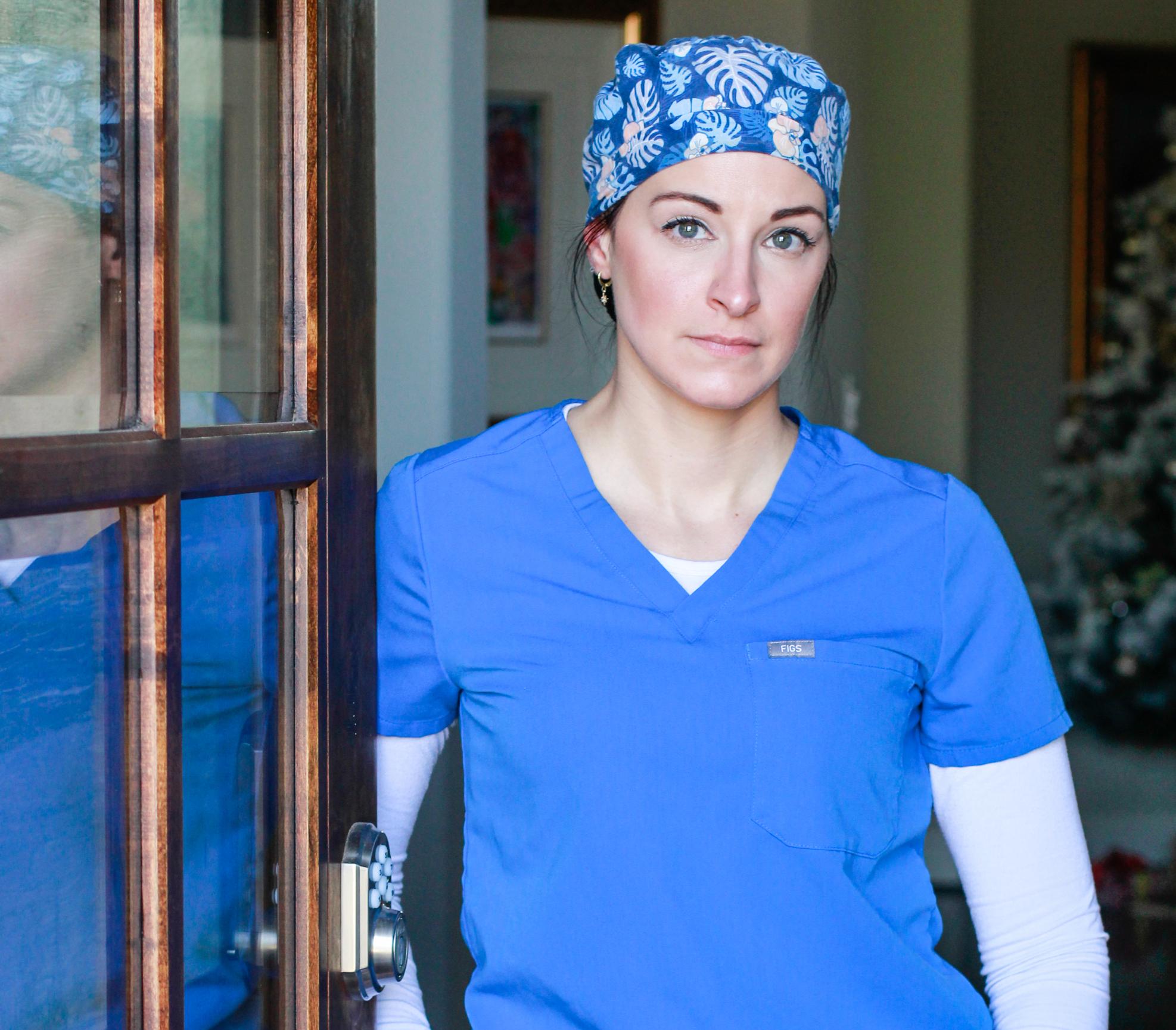 Krankenschwester Jennifer Gillen Fuller in blauer OP-Kleidung an der Tür zu ihrer Krankenstation
