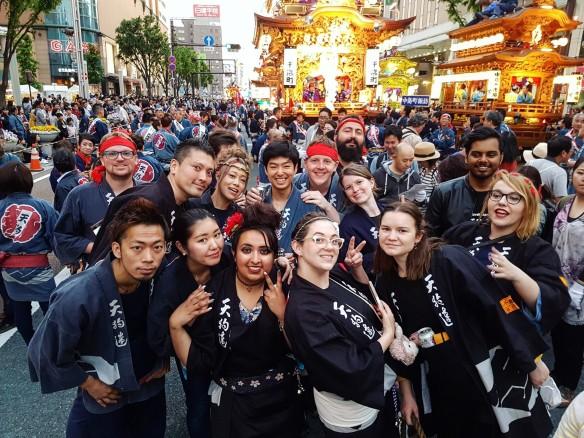 Farrah und eine multikulturelle Gruppe von Freundinnen und Freunden auf einem Straßenfest in Japan; alle tragen dunkle japanische Hemden mit japanischen Schriftzeichen, einige haben ein rotes Stirnband; sie lachen in die Kamera und zeigen das Peace-Zeichen mit den Händen