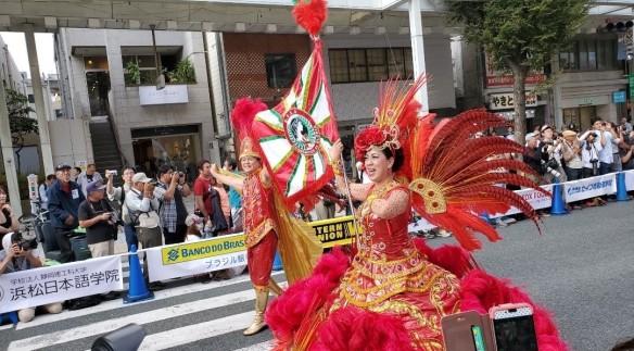 Zwei Samba-Tänzer - ein Mann und eine Frau - tanzen eine Straße in Japan hinunter, beide tragen traditionalle Sambakostüme in Rot mit Federn und einer Flagge; Zuschauer machen Fotos