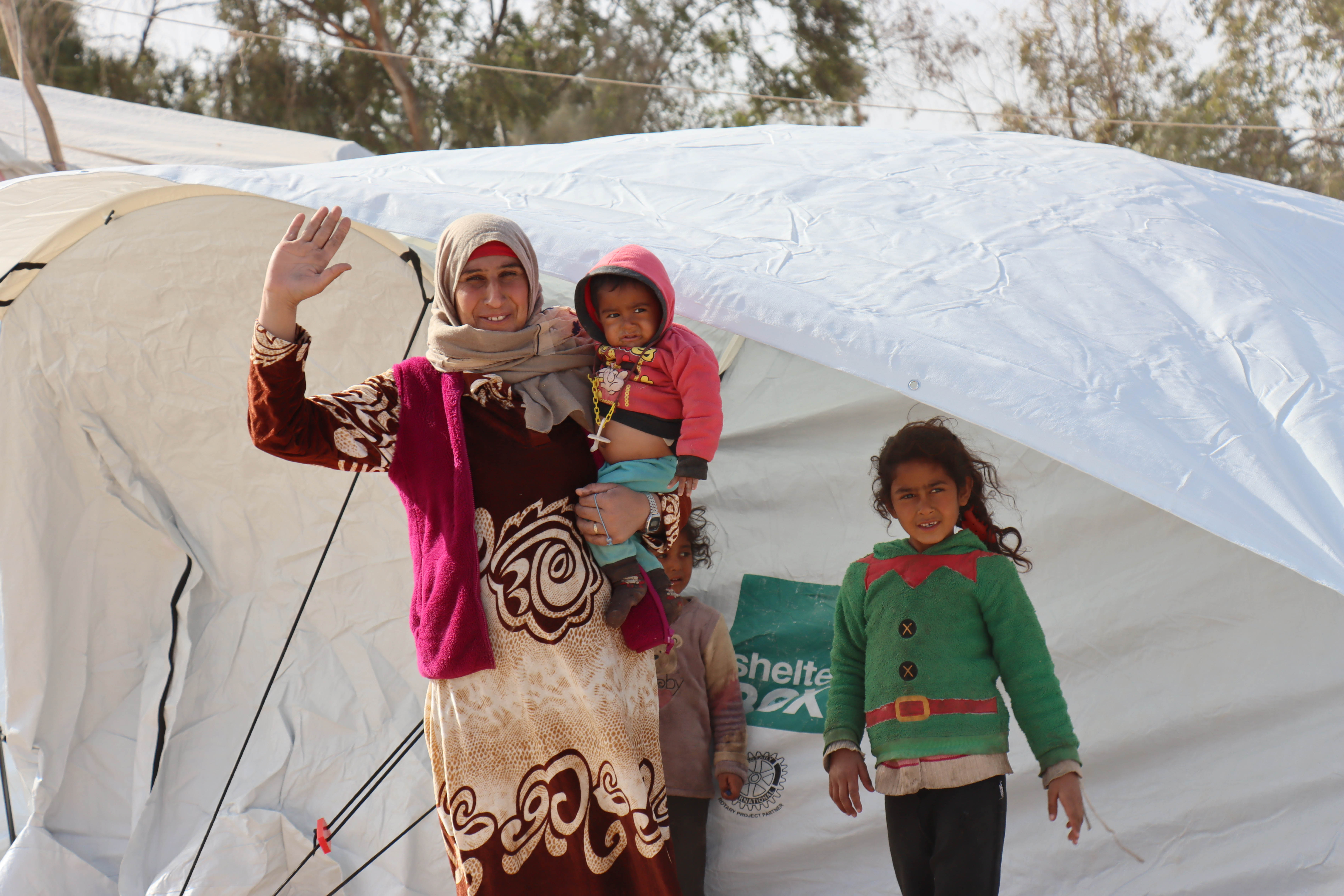 Eine syrische Mutter mit Kopftuch winkt lächlnd in die Kamera, auf dem Arm ein Baby und neben ihr ein junges Mädchen. Beide stehen vor einem weißen Zelt mit ShelterBox-Logo.