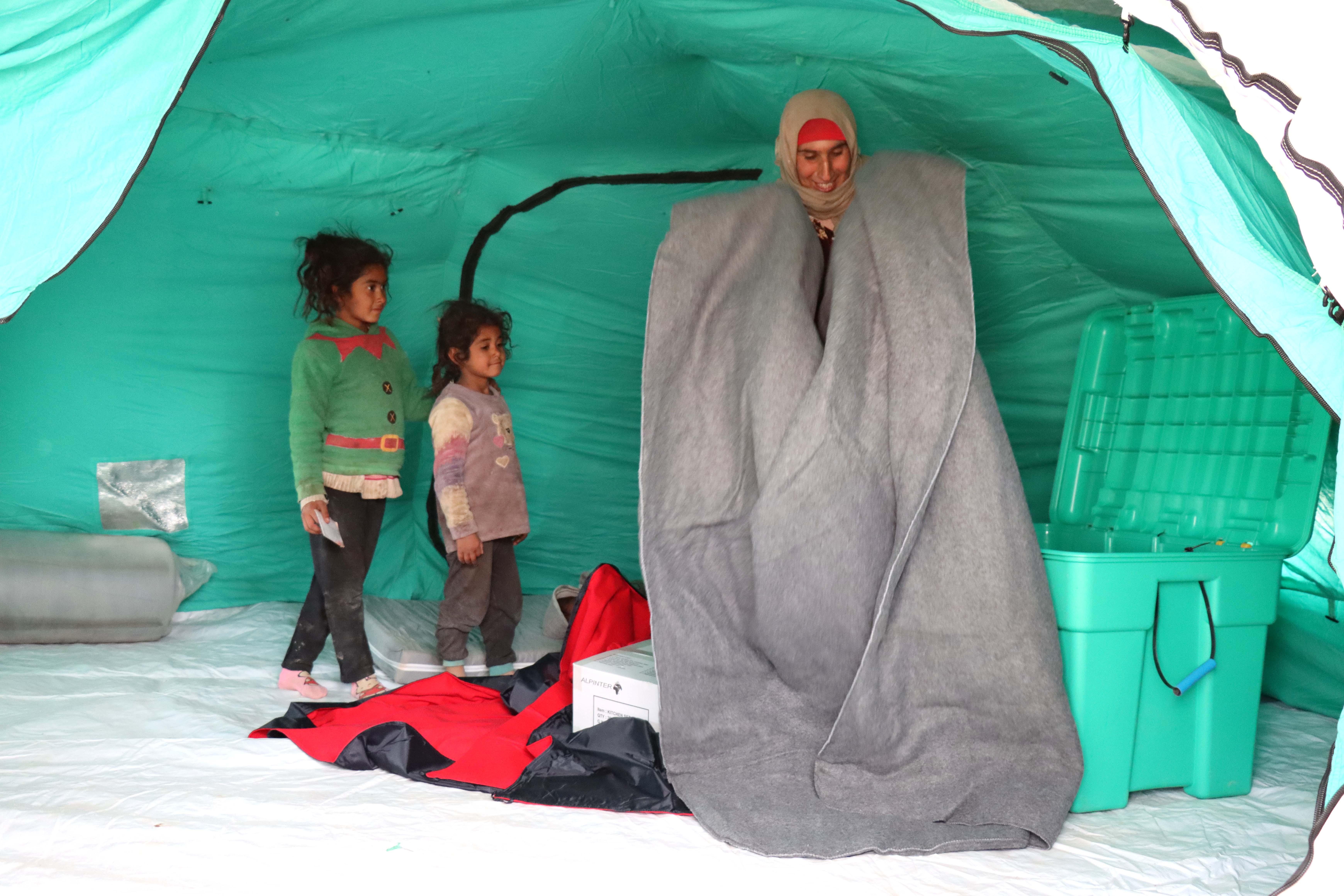 Eine Frau mit Kopftuch steht in einem Zelt und packt eine Decke aus einer großen grünen Kiste aus und lächelt. Zwei kleine Mädchen stehen neben ihr und bestaunen die Decke.