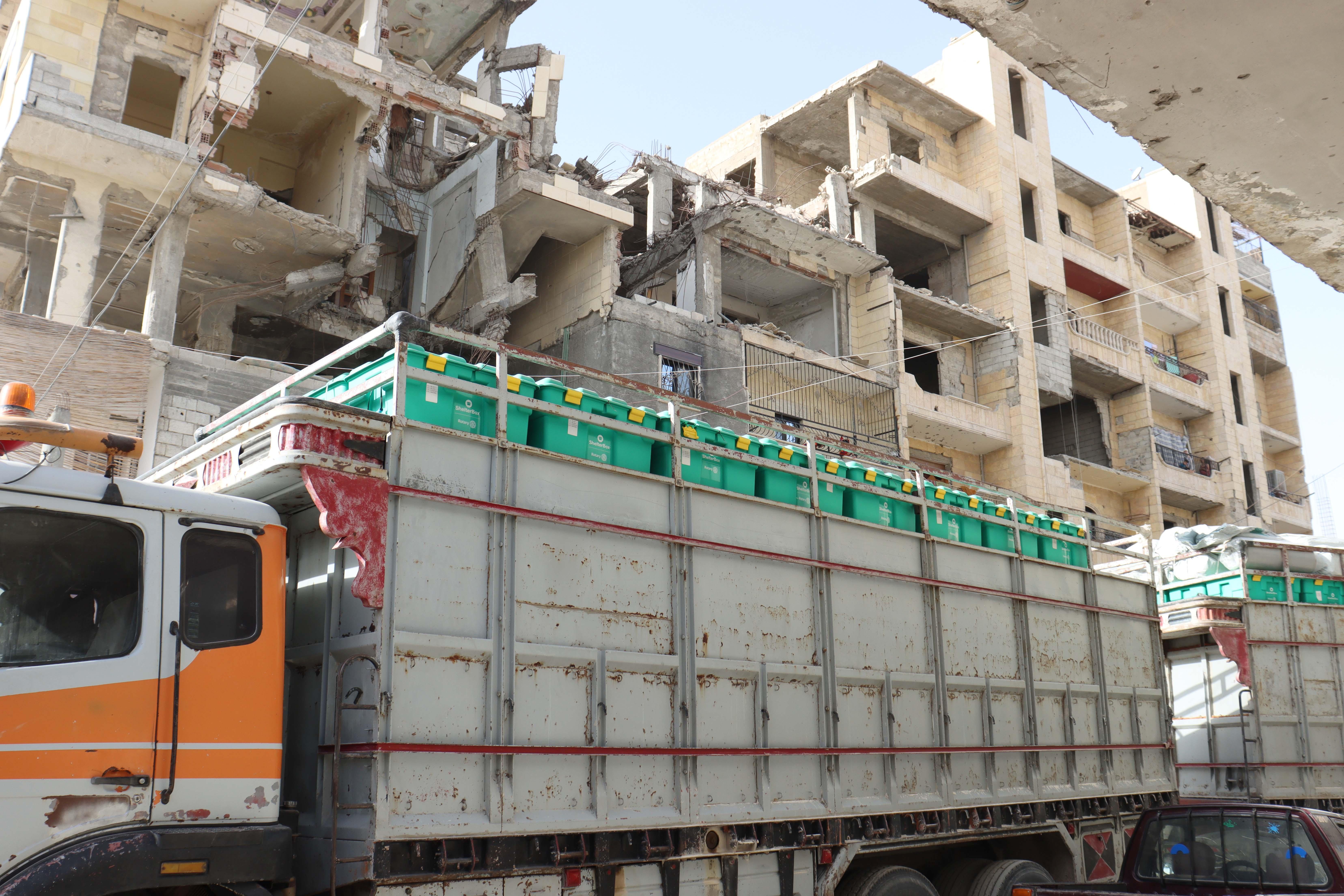 Ein Laster mit 2 Anhängern beladen mit vielen grünen ShelterBoxen fährt durch Häuserruinen ohne Fenster und mit größtenteils zerstörten Außenwänden.