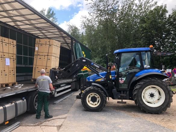 Man siegt einen blauen Traktor eine Palette mit Kartons von einem großen Lasteranhänger abladen. Ein Mann mit grüner Arbeitshose, grauem T-Shirt und Arbeitshandschuhen überwacht den Prozess.