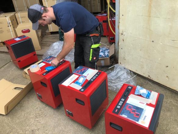 Ein Mann in dunkler Arbeitskleidung (Kargo-Hosen) klebt Schilder auf einen von 6 ausgepackten roten Bautrockner. Im Hintergrund sind viele Pappkartons zu sehen.n